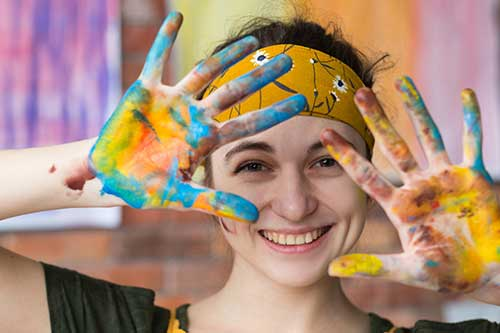 Woman smiling and showing her hands with paint on them